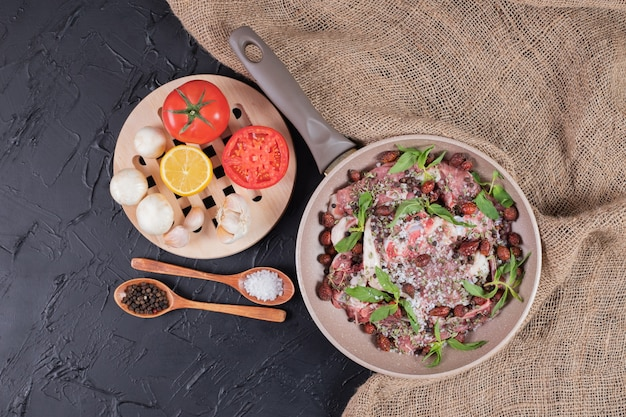 Salade de viande crue à la menthe fraîche dans une casserole et assiette de légumes frais.
