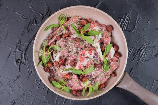 Salade de viande crue à la menthe fraîche dans une poêle sur une surface sombre.