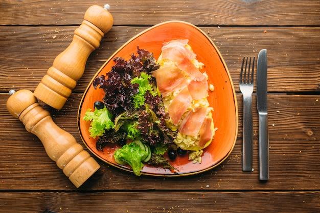 Salade de viande dans un bol, couteau, fourchette et poivrière sur table en bois, vue du dessus