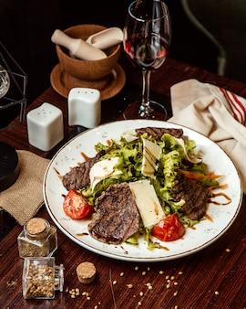 Salade de viande laitue tomate fromage vin rouge vue latérale