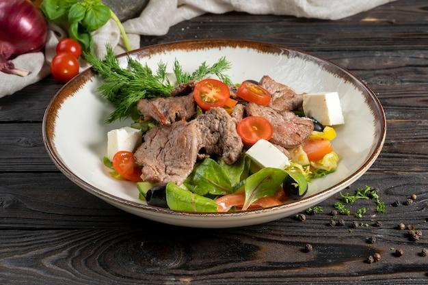 Salade de viande avec rosbif, feuilles de laitue, tomates cerises, fromage feta et olives.
