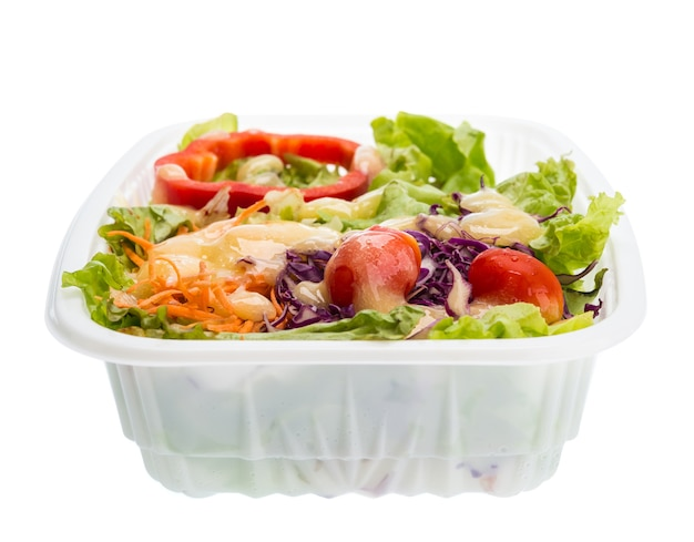 Salade avec vinaigrette dans un contenant en plastique isolé sur fond blanc