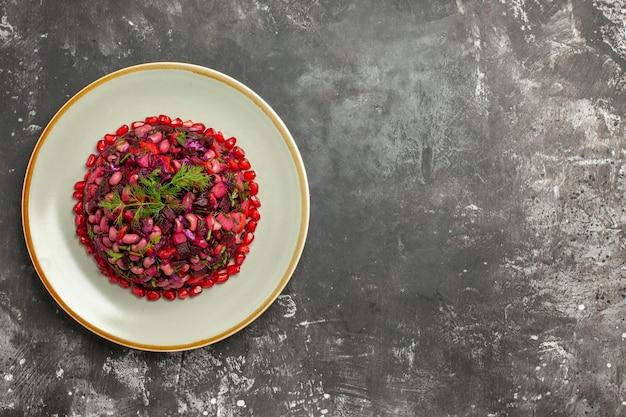 Salade de vinaigrette vue de dessus avec des grenades et des haricots sur une surface grise