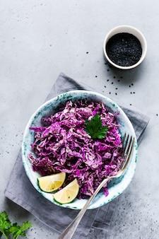 Salade violette crue fraîche dans un bol en céramique de chou chinois sur une vieille surface en béton gris. vue de dessus.