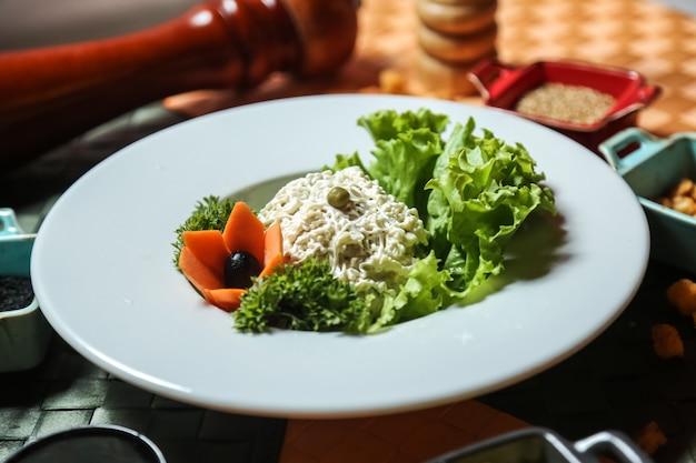Salade vue de face avec laitue mayonnaise et carottes comme décor sur une assiette