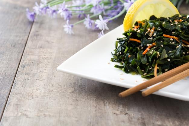 Salade de wakame avec carotte, graines de sésame et jus de citron sur l'espace de copie de table en bois