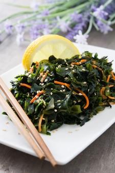 Salade de wakame avec carotte, graines de sésame et jus de citron sur table en bois