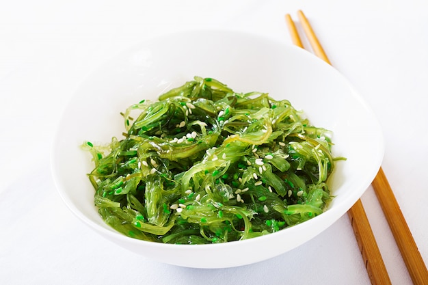 Salade wakame chuka ou algues aux graines de sésame dans un bol sur fond blanc.