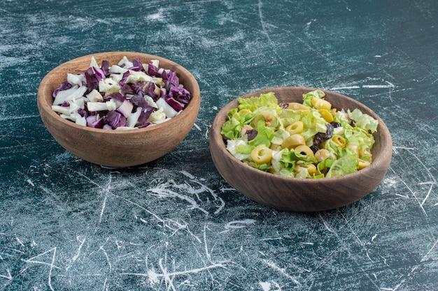 Salades de chou et de laitue dans des coupes en bois.