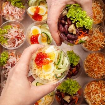 Salades dans des gobelets en plastique, restauration. nourriture livrée à domicile.