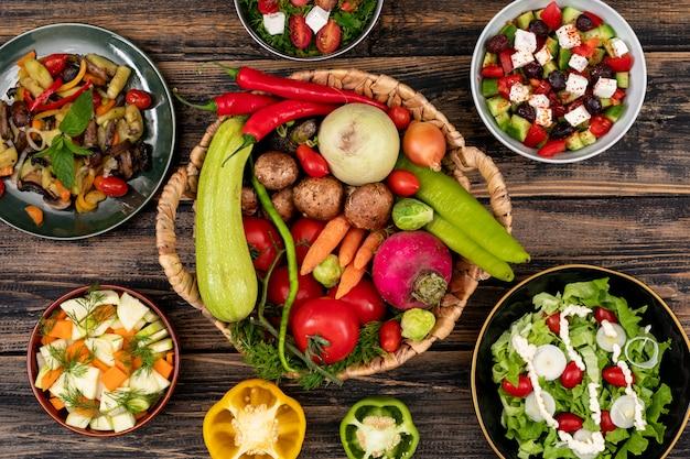 Salades de légumes sur le concept de vue de dessus de table en bois