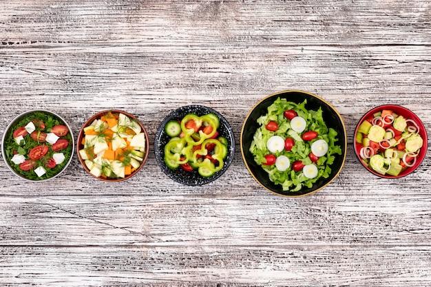 Salades de légumes sur la surface en bois vue de dessus