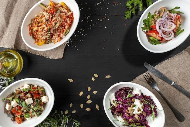 Salades de légumes verts viande et fromage sur fond de bois noir