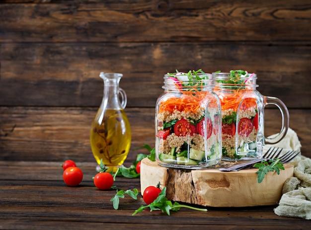 Salades de quinoa, roquette, radis, tomates et concombre dans des bocaux en verre sur dos en bois