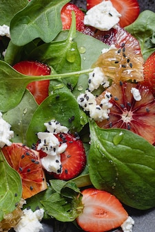 Saladier d'été avec épinards, fraise, fromage cottage, oranges sanguines et miel. fermer. schéma