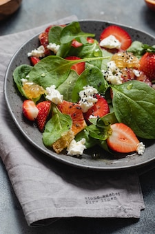 Saladier d'été avec épinards, fraise, fromage cottage, oranges sanguines et miel.