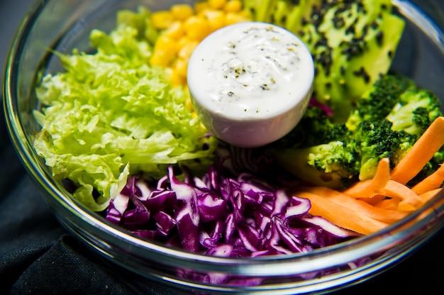 Saladier. ingrédients brocoli, maïs, carottes, couscous, laitue, chou, sauce.
