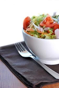 Saladier avec laitue, carotte, tomate et oignon