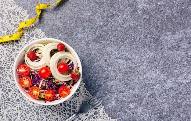 Saladier sain avec tomates légumes frais mélangés dans un plat et ruban à mesurer