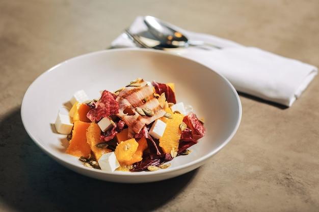 Saladier. savoureux saladier sain avec du fromage feta et du bacon debout sur la table à la cafétéria