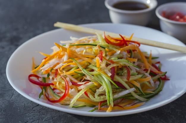 Saladier végétalien de style asiatique avec un mélange de légumes sur un fond sombre.
