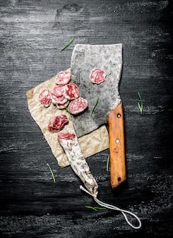 Salami à l'ail et une vieille hachette sur table rustique noire.