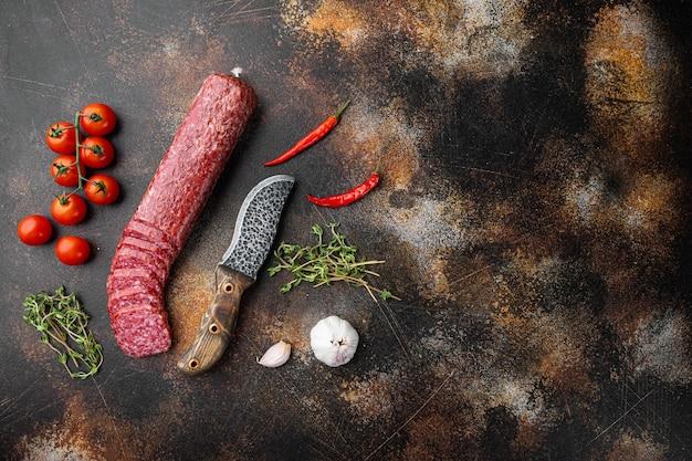 Salami au romarin frais et aux épices, sur fond de table rustique sombre, vue de dessus à plat, avec espace de copie pour le texte