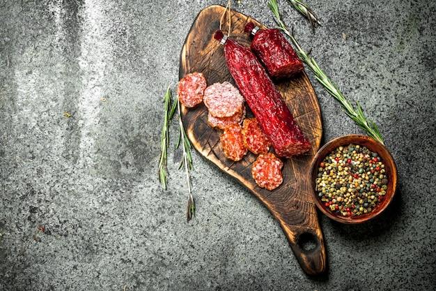 Salami aux épices et herbes. sur une table rustique.