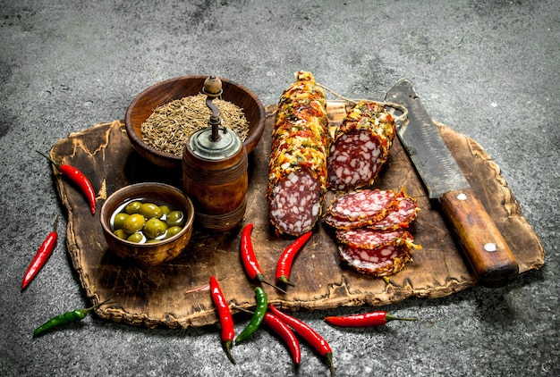 Salami aux épices et piments forts sur le plateau. sur une table rustique.
