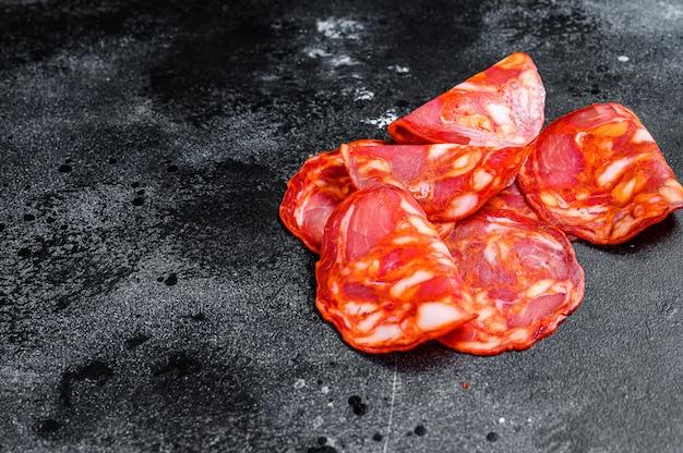 Salami de chorizo en tranches. saucisse chorizo traditionnelle espagnole. surface noire. vue de dessus. espace pour le texte