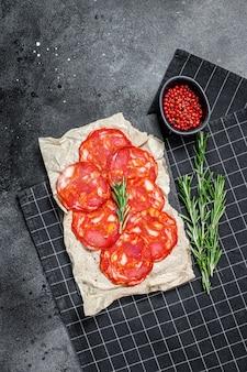 Salami de chorizo en tranches. saucisse chorizo traditionnelle espagnole. surface noire. vue de dessus