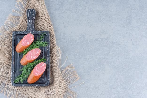 Salami frais avec des feuilles de fenouil sur une planche à découper noire.