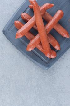 Salami frais sur une planche à découper en bois noir.