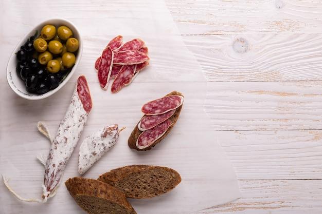 Salami et pain sur un fond en bois blanc. vue de dessus.