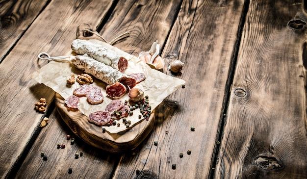 Salami parfumé à l'ail et aux épices sur table en bois.