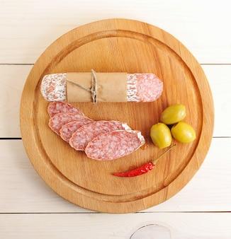 Salami, piment et olives sur une surface en bois
