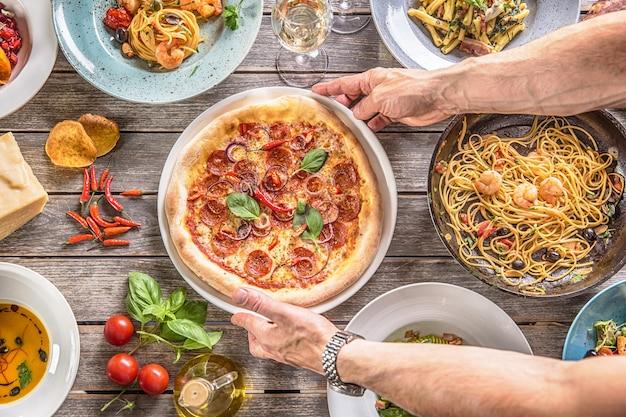 Salami pizza dans les mains du cuisinier. chef servant une pizza diavolo au milieu de la table pleine de plats italiens.