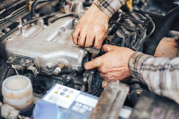 Sale mains de mécanicien automobile réparant voiture