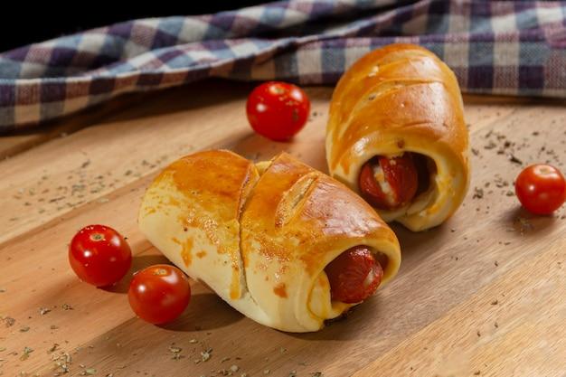 Salé avec saucisse hot dog et tomates. socle en bois et tissu à carreaux en toile de fond.