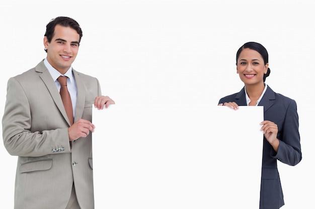 Salesteam souriant tenant une pancarte blanche