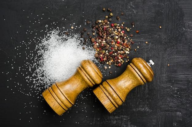 Salière et poivrière en bois. assaisonnement sel et poivre sur tableau noir
