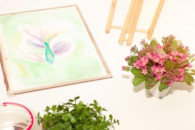 Salle d'art en temps de détente et petit pot pour fleur rose. poisson peinture dans le salon.