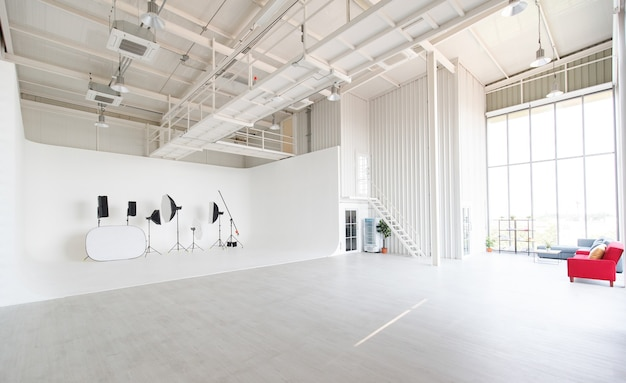 Salle d'atelier de studio de photographie de conception industrielle intérieure large et haute vide pleine d'espace et d'équipement de photographe professionnel placé sur un mur et un sol blancs avec des ampoules et un climatiseur.