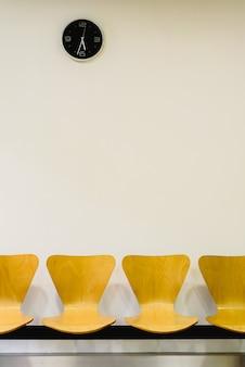 Salle d'attente avec des chaises en bois vides et horloge murale, concept en attente.