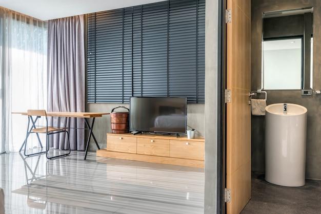 Salle de bain de luxe avec cuvette de toilette dans la chambre avec télévision et bureau
