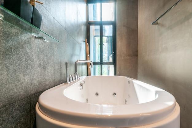 Salle de bain de luxe dotée d'une baignoire avec lumière et espace lumineux