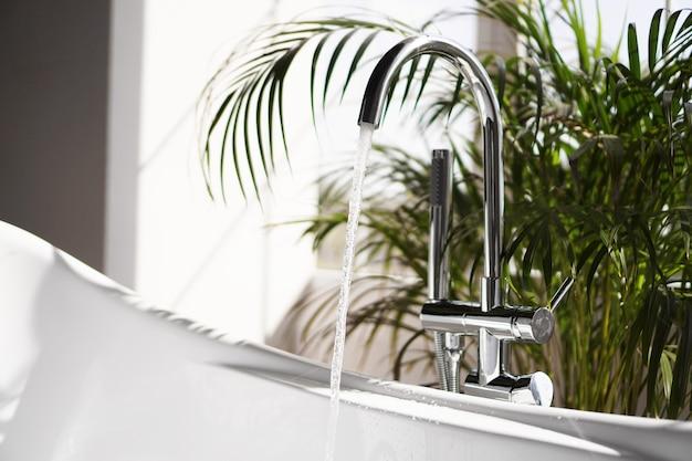 Salle de bain moderne. bain blanc avec des branches de palmiers verts. pièce lumineuse avec la lumière du soleil d'une grande fenêtre. l'eau coule d'un robinet