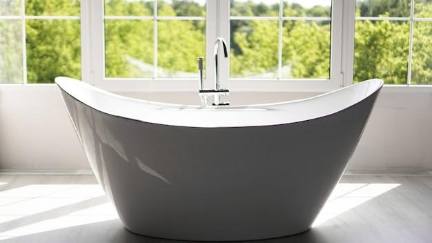 Salle de bain moderne dans un intérieur lumineux avec grande fenêtre et lumière ensoleillée