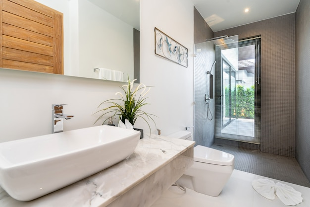 Salle de bain moderne, lavabo, douche et baignoire dans une villa de luxe