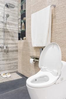 Salle de bain moderne et spacieuse avec des carreaux lumineux avec toilette et lavabo